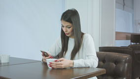 Beautiful girl in a cafe using phone and looking around. Professional shot on BMCC RAW with high dynamic range. You can use it e.g. in your commercial video stock video footage