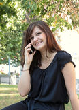 Beautiful girl call by phone in a park Stock Photo