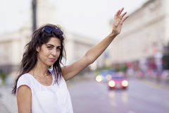 Beautiful girl calling taxi cab Stock Images
