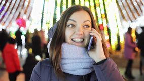 Beautiful girl calls friends on New Year`s Eve with congratulations, Christmas and New Year. `s celebration on the city Christmas tree stock video