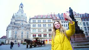 Beautiful girl calls in videocall through phone and shows online sights of European old city  Dresden on winter day i. Exquisite Young woman holding gadget and stock video footage