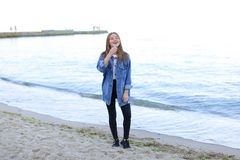 Portrait of cute young woman who poses and smiles in camera, sta Stock Photos