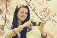 Beautiful girl with camera in spring park Stock Image