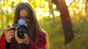 Beautiful girl with a camera walks through the autumn forest and takes pictures. Weekend outside the city. Weekend outside the city stock video footage