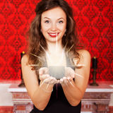 Beautiful girl with a candle in hands on red vintage background Royalty Free Stock Photo