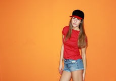 Beautiful girl in a cap and chert. Beautiful and young girl in a cap and chert stands near the orange wall Stock Image