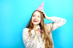 Girl in a cap and with a pipe. Beautiful girl in a cap and with a pipe on a blue background. Concept birthday Royalty Free Stock Image