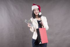 Beautiful girl cap santa package  shopping with a bundle of dollars. Beautiful girl cap santa package for shopping with a bundle of dollars Royalty Free Stock Image