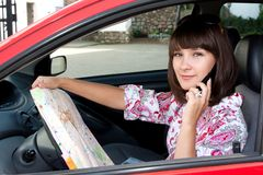 Beautiful girl in the car on the road map looks Royalty Free Stock Photo