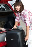 Beautiful girl in a car trunk loads Royalty Free Stock Image