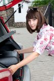 Beautiful girl in a car trunk loads, a big, heavy, Royalty Free Stock Photos