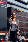 Beautiful girl in a cardigan, shirt and sunglasses outdoor. Beautiful girl with long hair in a cardigan and sunglasses with flowing hair on the background of the Stock Photography