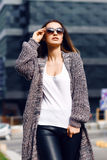 Beautiful girl in a cardigan, shirt and sunglasses outdoor. Beautiful girl with long hair in a cardigan and sunglasses with flowing hair on the background of the Royalty Free Stock Image