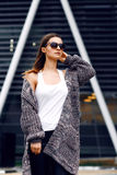 Beautiful girl in a cardigan, shirt and sunglasses outdoor. Beautiful girl with long hair in a cardigan and sunglasses with flowing hair on the background of the Stock Image