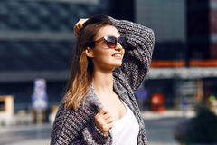 Beautiful girl in a cardigan, shirt and sunglasses outdoor. Beautiful girl with long hair in a cardigan and sunglasses with flowing hair on the background of the Royalty Free Stock Photography