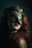 Beautiful  Girl in Carnival mask with long curly hair. Masquerade Holidays Stock Photos