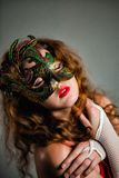 Beautiful  Girl in Carnival mask with long curly hair. Masquerade Holidays Stock Images