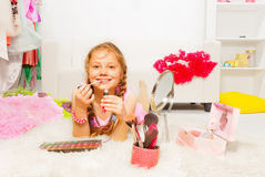 Beautiful girl on carpet and applying lip gloss Stock Photos