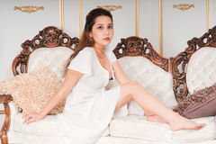 Beautiful girl on a carved loveseat Royalty Free Stock Photo