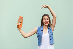 Beautiful girl in casual style with orange bottle of water on green background. Beautiful funny young woman with freckles in casual style hold a bottle of water Stock Image