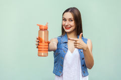 Beautiful girl in casual style with orange bottle of water on green background. The pretty young woman with freckles in casual style holding a bottle of water Royalty Free Stock Photo