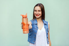 Beautiful girl in casual style with orange bottle of water on green background. Beautiful young woman with freckles and denim jacket in casual style holding a Stock Photos