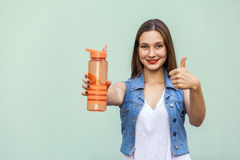 Beautiful girl in casual style with orange bottle of water on green background. Beautiful young woman with freckles in casual style looking at camera and shows Stock Photography