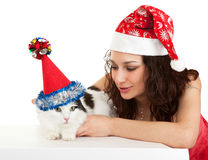 Beautiful girl with a cat in New Year's caps. Stock Images