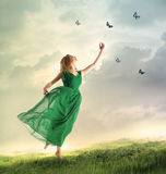 Beautiful girl catching butterflies on a mountain. Beautiful woman in a green dress chasing butterflies on a mountain Stock Images