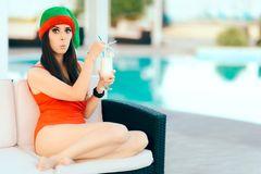 Christmas Woman Spending Holidays Drinking Cocktail by the Pool. Beautiful girl celebrating Xmas in a spa resort Royalty Free Stock Images