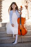 Beautiful girl with a cello stands on the steps
