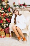 Beautiful girl in the chair near the Christmas tree and fireplace. New Year, toned image, the author`s processing.  Royalty Free Stock Images