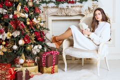 Beautiful girl in the chair near the Christmas tree and fireplace. New Year, toned image, the author`s processing.  Royalty Free Stock Image