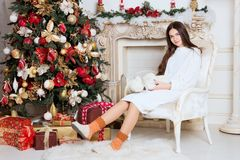 Beautiful girl in the chair near the Christmas tree and fireplace. New Year, toned image, the author`s processing.  Stock Photography