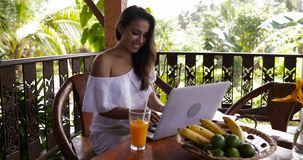 Beautiful girl chatting on laptop computer on summer terrace drinking juice, happy woman surfing web outdoors in morning stock video
