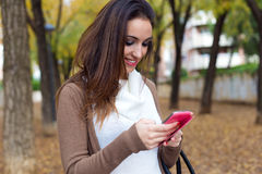 Beautiful girl chatting with mobile phone in autumn. Royalty Free Stock Images