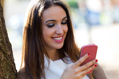 Beautiful girl chatting with mobile phone in autumn. Royalty Free Stock Photos
