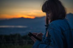 Beautiful girl chatting on smartphone at sunset over the lake royalty free stock images