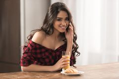Beautiful girl in checkered shirt eating croissant and drinking orange juice. For breakfast stock images