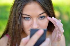 Beautiful girl checking her makeup outdoor Stock Photos