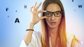 Beautiful girl checks vision in an ophthalmologist with glasses stock video footage