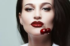 Beautiful girl with cherries in her mouth