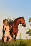 Beautiful girl with chestnut horse in evening field Royalty Free Stock Photography
