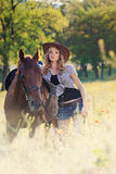 Beautiful girl with chestnut horse in evening field Stock Photo