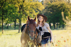 Beautiful girl with chestnut horse in evening field Royalty Free Stock Photo