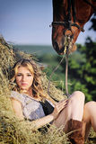 Beautiful girl with chestnut horse in stack of hay Royalty Free Stock Images