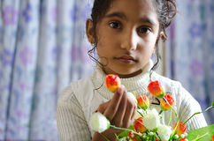 Beautiful girl child looking into camera flowers in hand Royalty Free Stock Photography