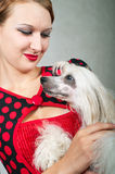 Beautiful girl and chinese crested dog. The beautiful girl and chinese crested dog on grey background. Shallow DOF, focus on girl stock image