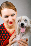 Beautiful girl and chinese crested dog. The beautiful girl and chinese crested dog on grey background. Shallow DOF, focus on girl stock photos