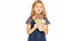 Beautiful girl with chocolate. Beautiful blonde girl in a blue dress with curls eating a chocolate Royalty Free Stock Image